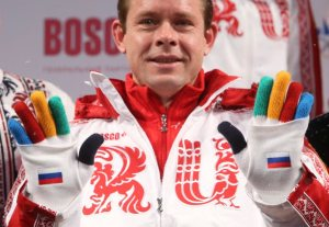Former Russian ice-hockey player Bure shows a pair of gloves during a presentation of Russia's uniform for the Sochi 2014 Winter Olympics in Moscow